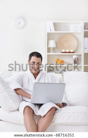 A young man in a white robe with laptop - stock photo
