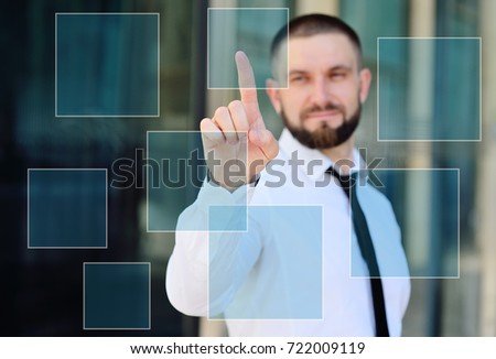 a young man in a white shirt and tie is pressing his index finger on the virtual screen of the touch screen on the background of a glass office building