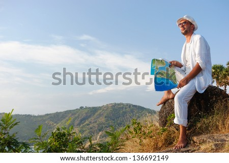A young man in a white suit sitting on the beach with a map - stock photo