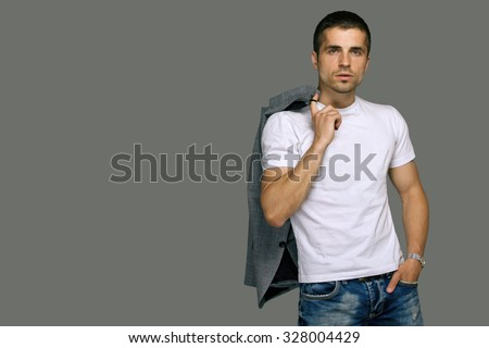 a young man in a white T-shirt and jeans, studio portrait - stock photo