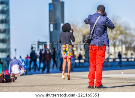 A young man in bright red trousers taking a photo with a lady in colorful shorts walking in front of him - stock photo