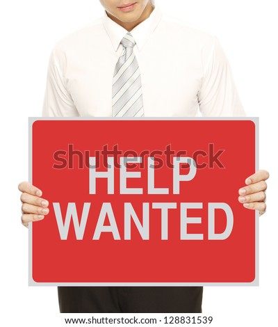 A young man in business attire holding a Help Wanted signboard
