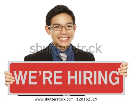 A young man in business attire holding a hiring sign - stock photo