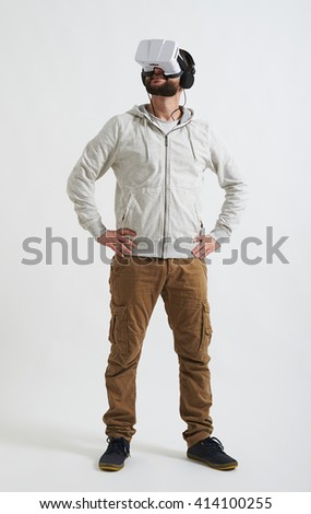 A young man in casual clothes is watching something in virtual reality glasses and wearing headphones on his head - stock photo
