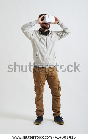 A young man in casual clothes is watching something using virtual reality glasses