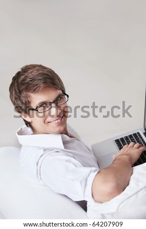 A young man in glasses with a laptop - stock photo