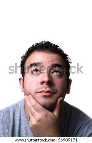 A young man in his middle 20s with his hand on his chin looks like he is thinking deeply about something. - stock photo