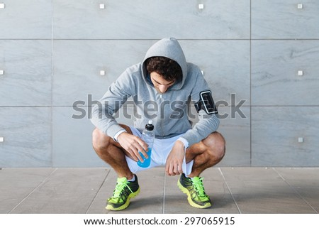 A young man in sportswear resting in the shade of a building in a summer day, drinking an energy drink blue color from a bottle before resuming training - stock photo