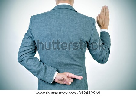 a young man in suit swearing an oath, rising his right hand, crosses his fingers in his back - stock photo