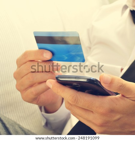 a young man in suit using his credit card to shop online with his smartphone - stock photo