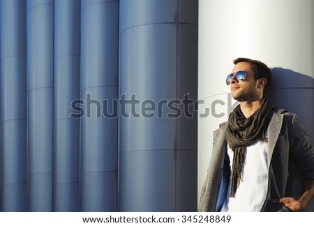 a young man in sunglasses, stylishly dressed on the modern building background. sunset in the city