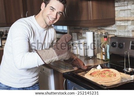 A Young man in the kitchen enjoying pizza - stock photo