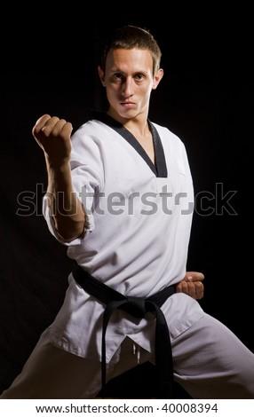 a young man in white kimono ready to fight on black background - stock photo