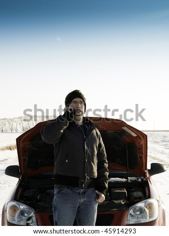 A young man is calling for help on his cell phone, while standing in front of a red car with it's hood up.  Copyspace is available on the top half of the image. - stock photo