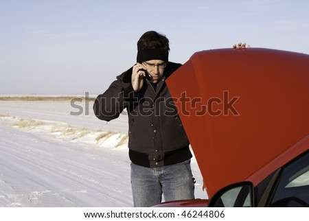 A young man is checking under the car hood while talking on a cell phone. - stock photo