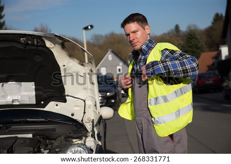 A young man is fitting his reflective vest to protect himself. - stock photo