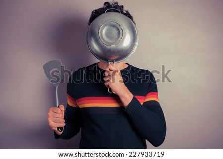 A young man is hiding his face behind a colander - stock photo