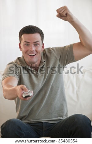 A young man is holding a remote and watching television.  He is smiling at the camera.  Vertically framed shot. - stock photo