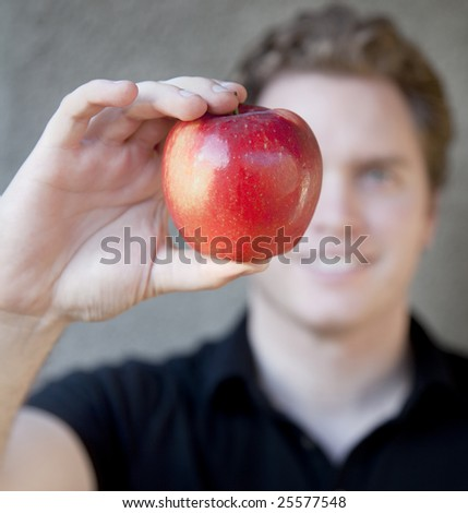 A young man is holding an apple up to his eye with the apple covering some of his face in front of his eye - stock photo