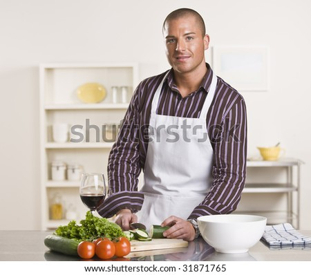 A young man is in his kitchen and is chopping vegetables to prepare a meal.  He has a glass of wine and is looking at the camera.  Horizontally framed shot. - stock photo