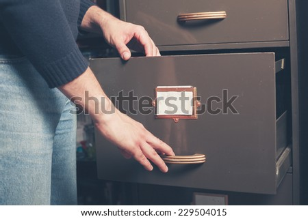 A young man is opening a file cabinet - stock photo
