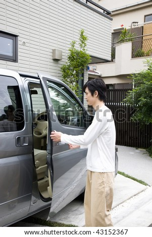 A young man is opening the car door