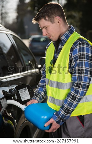 A young man is refueling his car with a blue plastic canister. - stock photo