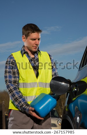 A young man is refueling his car with a blue plastic canister at a sunny day. - stock photo
