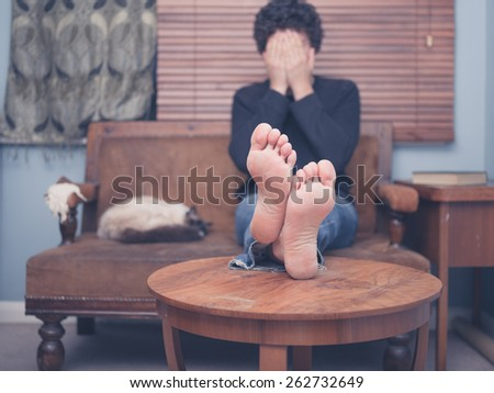 A young man is resting his bare feet on a coffee table while he is sitting on a sofa with his head in his hands - stock photo