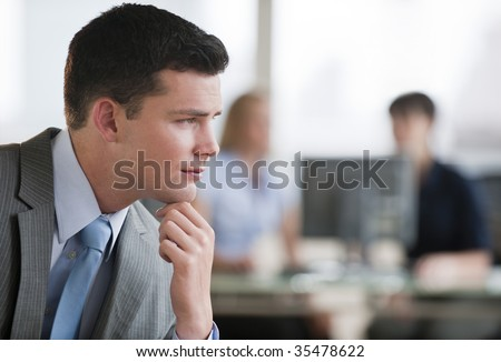 A young man is seated in an office and is looking away from the camera.  Horizontally framed shot. - stock photo