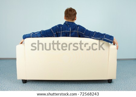 A young man is sitting comfortably at home on the couch - stock photo