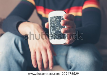 A young man is sitting on a sofa and is holding a broken smart phone with a cracked screen - stock photo