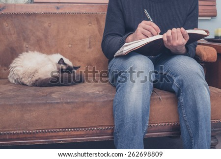 A young man is sitting on a sofa with a cat and is writing in a notebook