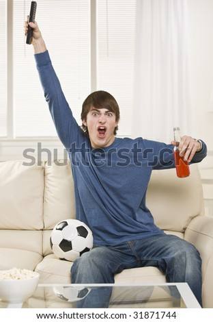 A young man is sitting on the couch in his living room and watching a sports game.  He is holding a remote control, a soda, and there is a soccer ball right next to him. Vertically framed shot. - stock photo