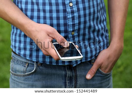A young man is using a smartphone by tipping with his fingers - stock photo