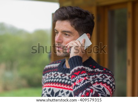 A young man is using his phone in a rustic atmosphere - stock photo