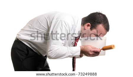 A young man is vomiting into a pail after eating a bad corn dog and getting food poisoning, isolated against a white background. - stock photo