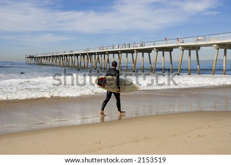 a young man is walking along the beach ready to go surfing - stock photo
