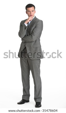 A young man is wearing a business suit and looking at the camera.  Vertically framed shot. - stock photo