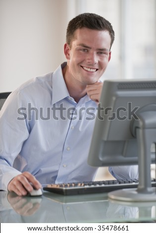 A young man is working on a computer and smiling at the camera.  Vertically framed shot. - stock photo