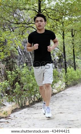 A young man jogging at a public park - stock photo