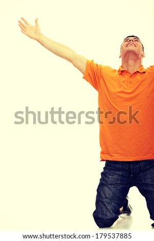 A young man joyously throws his hands up in the air. - stock photo