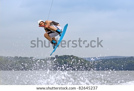 A young man jumps the wake behind a boat. - stock photo