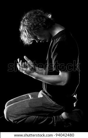 A young man kneels and prays - stock photo