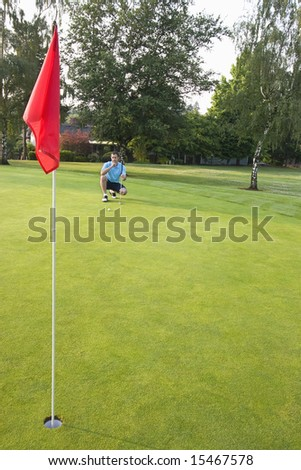 A young man, kneels, concentrating, attempting to line up his golf shot. Vertically framed shot.