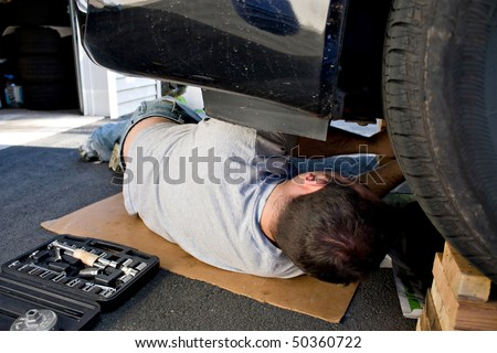 A young man laying underneath a car doing repairs or maintenance on the vehicle. - stock photo