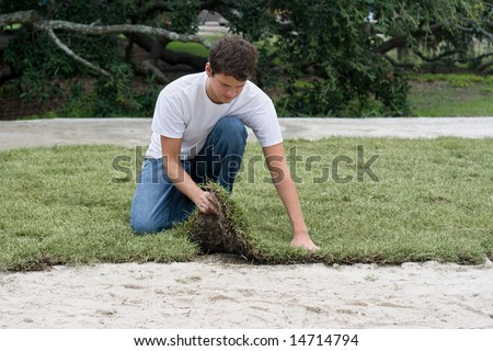 a young man lays sod over a sand bed