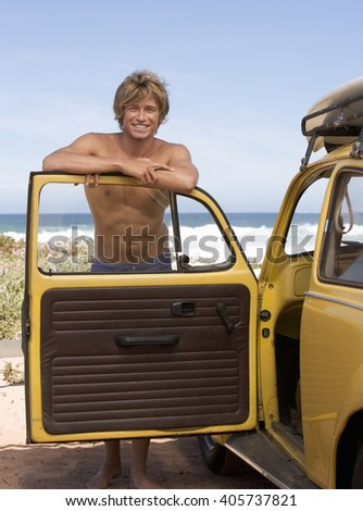 A young man leaning on the door of a car - stock photo