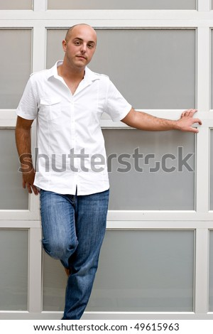 A young man leaning up against a wall hanging out in the city.