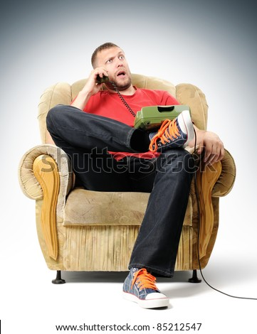 A young man listens to bad news over the phone - stock photo